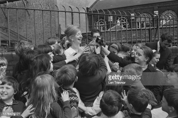 Biddy Baxter, the programme editor of children's television show 'Blue Peter', with a group of schoolchildren and the Blue Peter Siamese cat Jason,...
