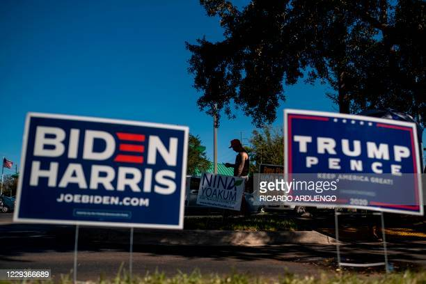 Biden and Trump campaign signs are displayed as voters line-up to cast their ballots during early voting at the Alafaya Branch Library in Orlando,...