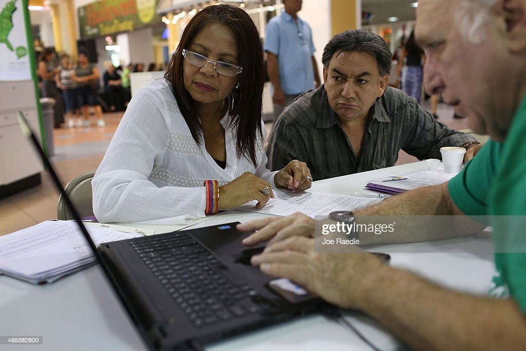 Bienvendida Barreno (L) and Jorge Baquero (C) listen as Antonio Galis, an insurance agent from Sunshine Life and Health Advisors, discusses plans available in the third year of the Affordable Care Act at a store setup in the Mall of the Americas on November 2, 2015 in Miami, Florida. Open Enrollment began yesterday for people to sign up for a 2016 insurance plan through the Affordable Care Act.