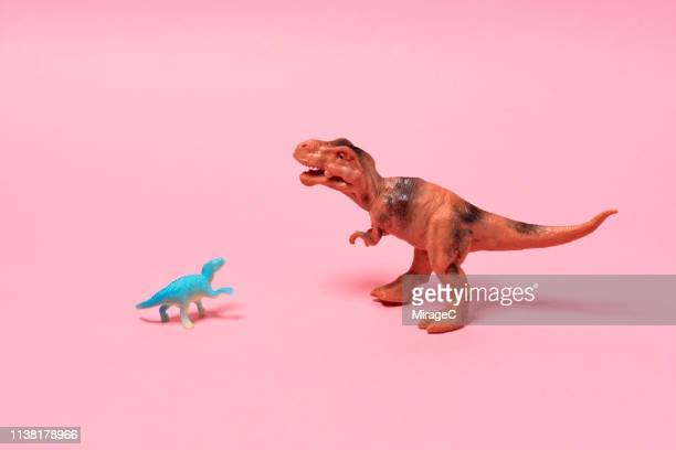 big and small toy dinosaurs - comparison stock pictures, royalty-free photos & images