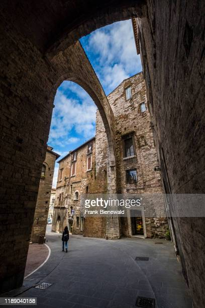 Big arches crossing over a small alley with stone houses in the medieval town.