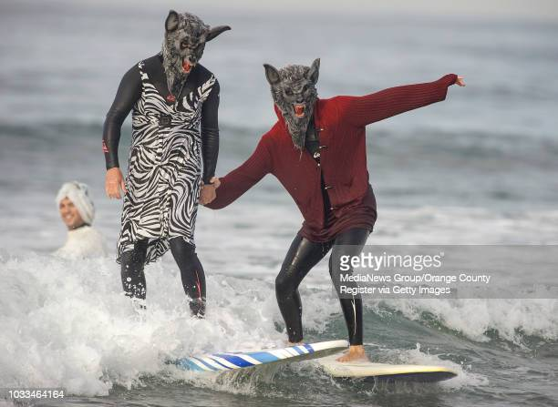 Big Bad Wolf Dave Granola left keeps Little Red Riding Hood son Zach safe in the surf during Blackies Halloween event in Newport Beach on Saturday...
