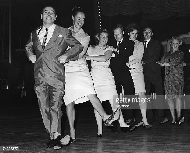 Big Bandleader Joe Loss introduces the Finnjenka, a Finnish version of the Conga, at the Hammersmith Palais, 22nd October 1964. He is publicising his...