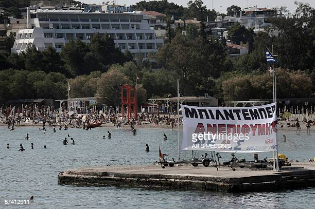 """Big banner reading """"Bilderberg Unwelcome"""" is placed at the beach of Vouliagmeni by members of right-wing nationalist Popular Orthodox Rally near the..."""