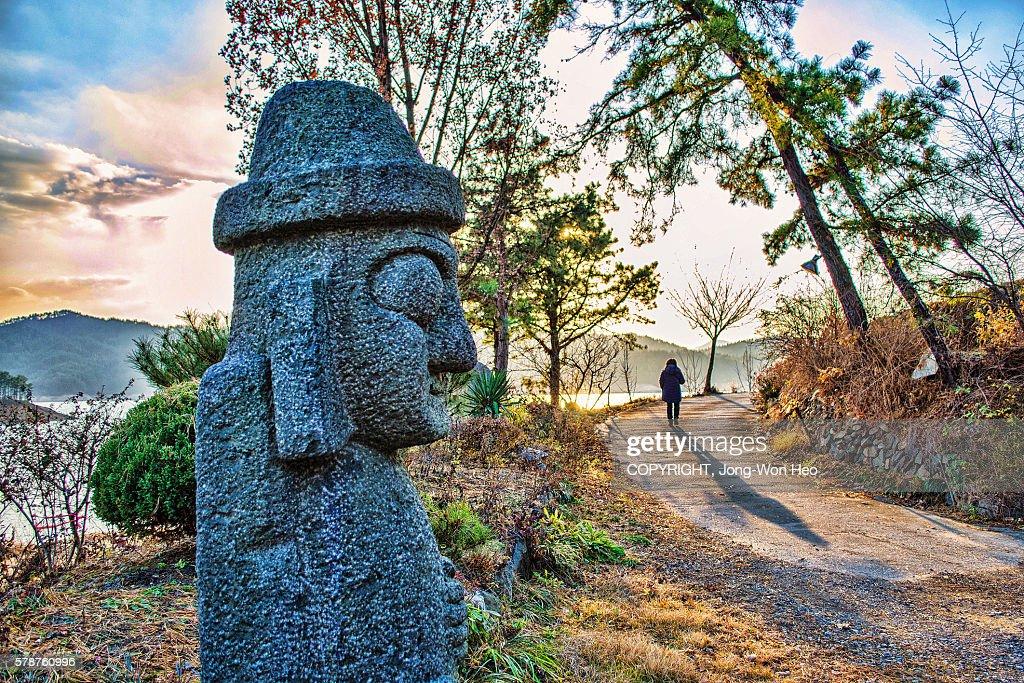 A big basalt doll saying 'bye' to a leaving woman : Stock Photo