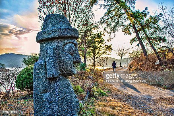 a big basalt doll saying 'bye' to a leaving woman - jeju stock photos and pictures
