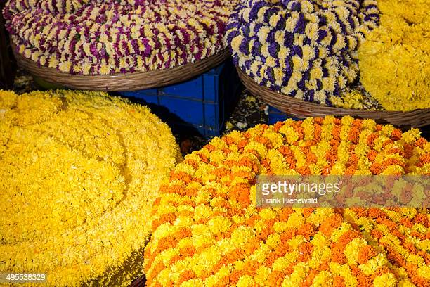 Big baskets full of yellow and orange marigold flowers for devotional use are for sale in the market