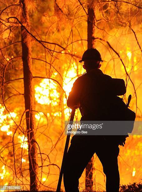 Big Bear firefighter Jon Curtis keeps a close eye on a 'slop over' fire that jumped Hwy 120 just east of Hardin Flat Road while fighting the Rim Fire...