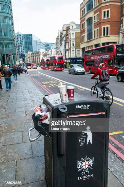 Big Belly Solar litter bin overflowing with rubbish in a City of London street.