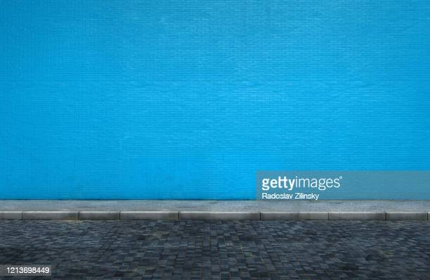 big blue brick wall on street with sidewalk - sidewalk stock pictures, royalty-free photos & images