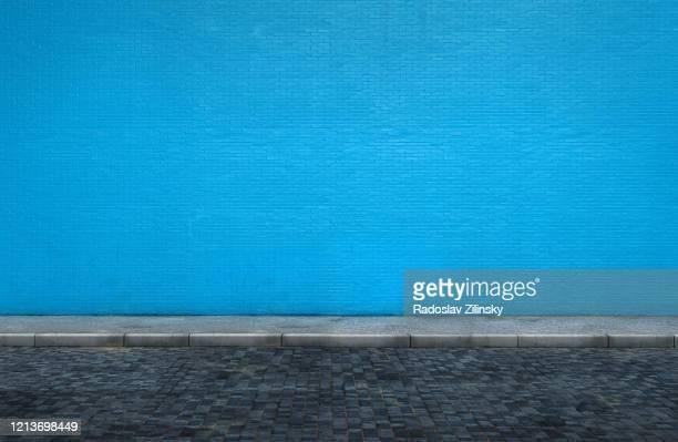 big blue brick wall on street with sidewalk - gehweg stock-fotos und bilder
