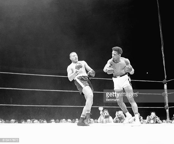 """Big Bob Baker leans back to evade the hurricane of blows from Tommy """"Hurricane"""" Jackson in the third round of their heavyweight go at the Garden..."""