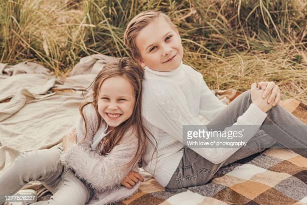 big brother and little sister children walking outdoors enjoying autumn season in a village - september stock-fotos und bilder
