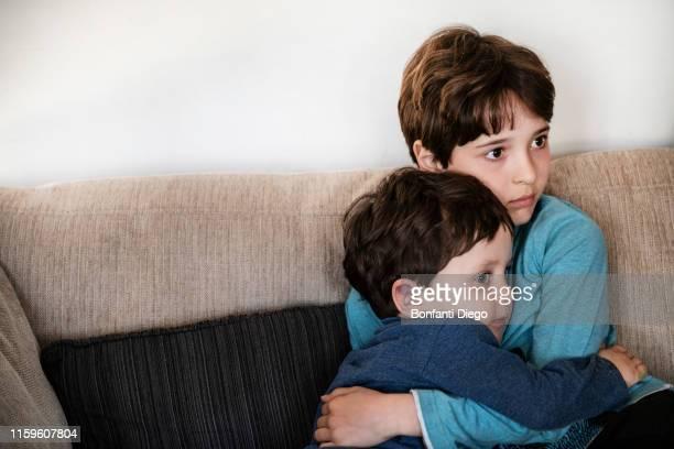 big brother hugging toddler, staring in disbelief on sofa - fratello foto e immagini stock
