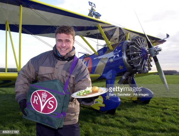 Big Brother winner Craig Phillips wingwalking on a 1940 Boeing Stearman biplane before delivering a Women's Royal Voluntary Service meal at Rendcomb...