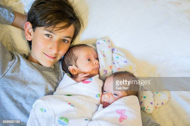 big brother with twin baby sister and brother - tied to bed stock pictures, royalty-free photos & images