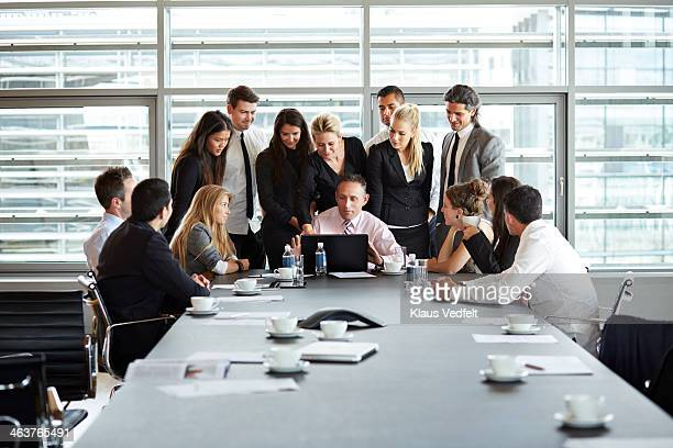 big business people group squeezing around laptop - surrounding stock pictures, royalty-free photos & images