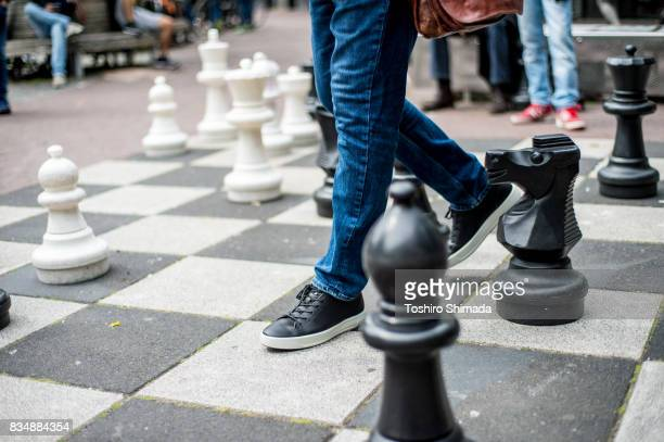 big chess and players in leidseplein, netherland - metaphase stock pictures, royalty-free photos & images