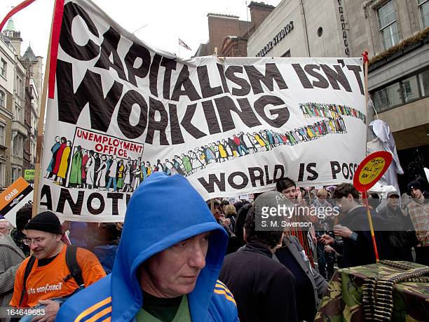 Big colourful banner is being held up that reads 'Capitalism isn't working'. Protesters are scattered about underneath. This is the big anti-cuts...