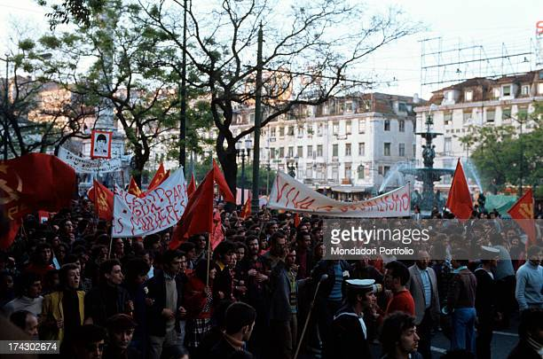 Big communist demostration of workers in a square of Lisbon; some banners writings Long live socialism and Same salary for women . Lisbon , 1974..