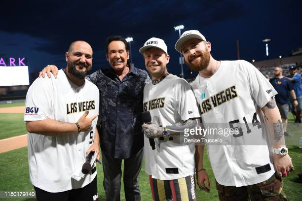 Big D Wayne Newton Ben McKee and Daniel Platzman of Imagine Dragons lead the soldout stadium in a singing of the traditional ÒTake Me Out to the...