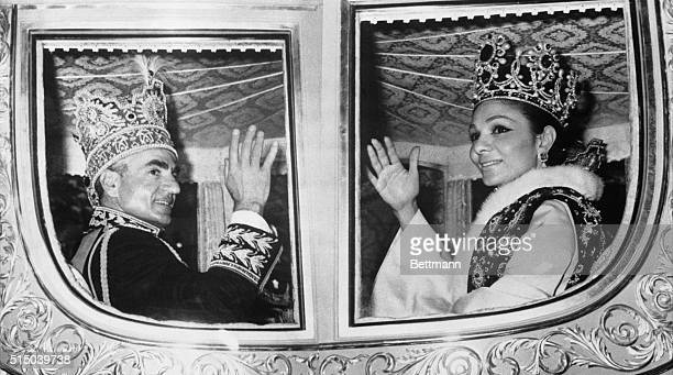 The shah of Iran and Empress Farah wave from their carriage as they ride through the streets of Tehran after their coronation ceremony The shah's...