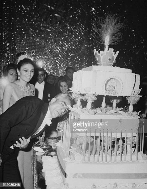 Big Day. Tehran, Iran: The shah of Iran blows out the 48 candles on his birthday cake in Tehran. His queen, Empress Farah, watches. The shah crowned...