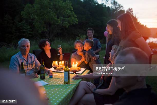 "big dinner: grandmother celebrating birthday outdoors at dusk. - ""martine doucet"" or martinedoucet stock pictures, royalty-free photos & images"