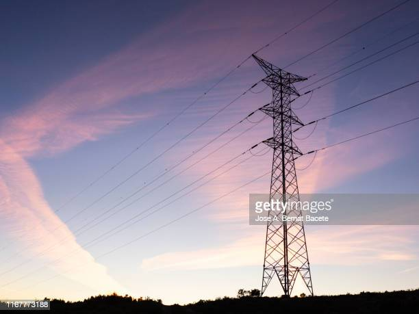big electrical towers of high tension for the distribution of electricity in a sunset in the mountain. - elettricità foto e immagini stock