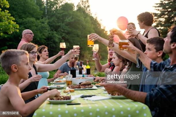 big family barbecue gathering at sunset, summer outdoors. - large family stock pictures, royalty-free photos & images