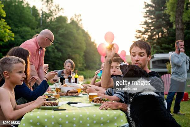 Big family barbecue gathering at sunset, summer outdoors.