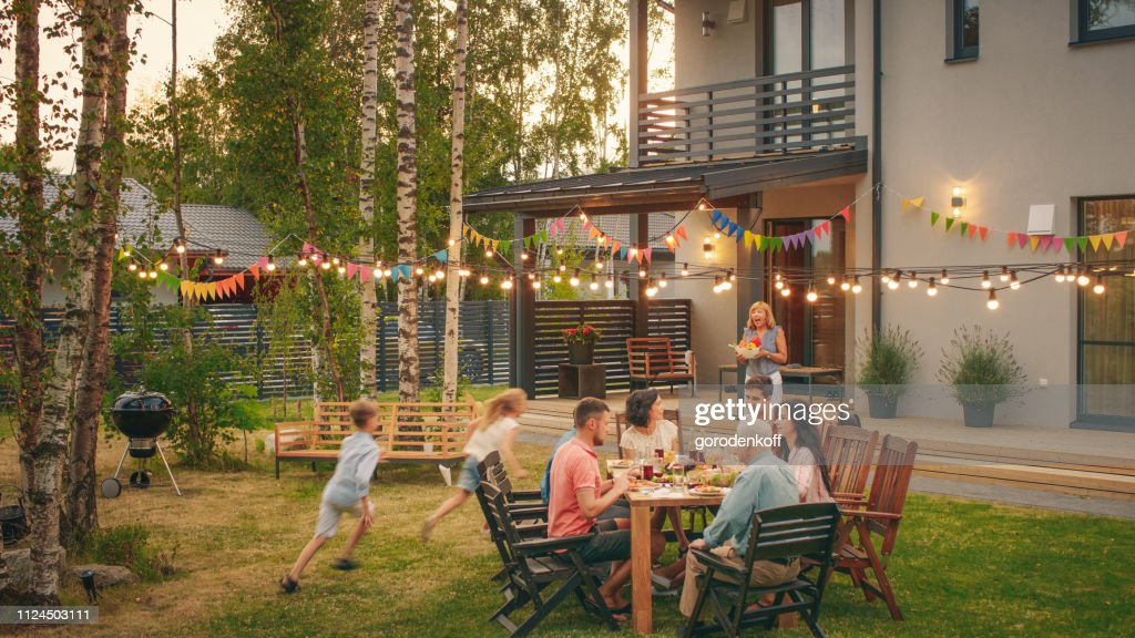 Big Family Garden Party Celebration, Gathered Together at the Table Family, Friends and Children. People are Drinking, Passing Dishes, Joking and Having Fun. Kids Run Around Table. : Stock Photo