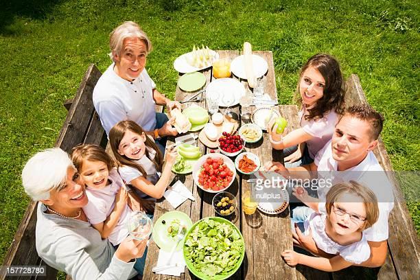 Gran familia tener un picnic en el jardín