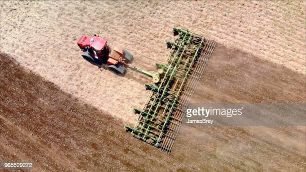 Big farm tractor tilling dusty Springtime fields.