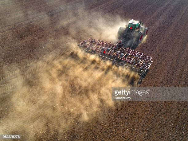 big farm tractor tilling dusty springtime fields. - tractor stock pictures, royalty-free photos & images