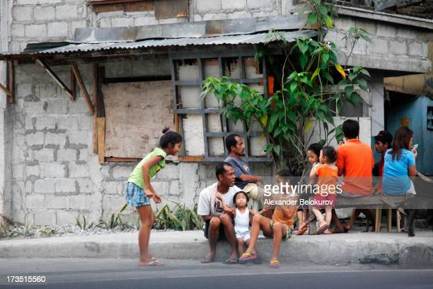 Big Filipino family enjoying free evening time with kids outside their house on the streets of Manila city, the Philippines. Several adults and kids...