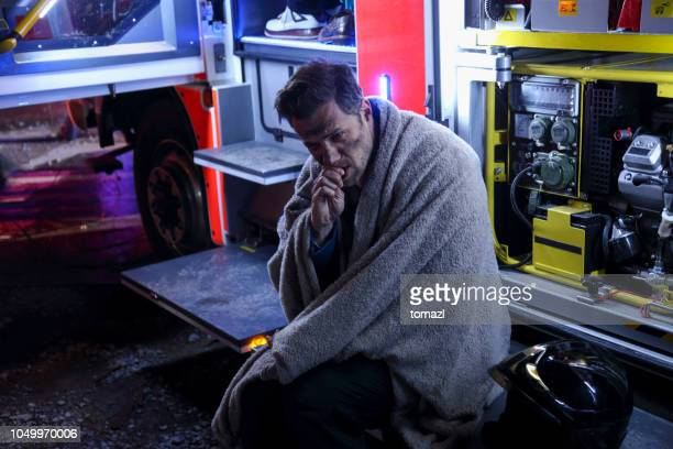 big fire victim sitting on a firefighter's truck - burns victims stock pictures, royalty-free photos & images
