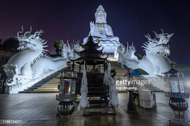 """big goddess statue named """"guanyin"""" one of iconic landmark of wat huay pla kang temple in chiang rai province of thailand after sunset. - guanyin bodhisattva foto e immagini stock"""