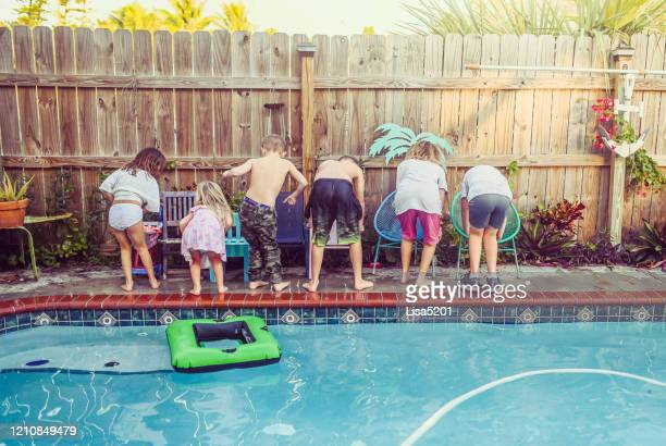 big group of children different ages sit by a pool acting silly - big bums stock pictures, royalty-free photos & images