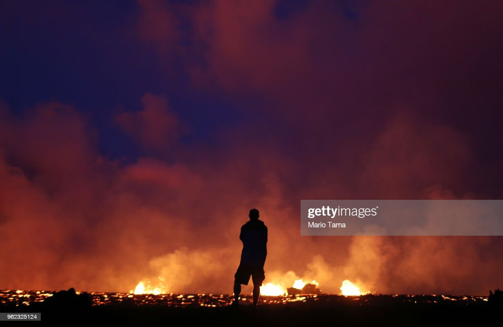 Big Island resident Shawn Krcma stands on newly hardened lava to catch a view as lava erupts and flows from a Kilauea volcano fissure in the vicinity of Leilani Estates, on Hawaii's Big Island, on May 24, 2018 in Pahoa, Hawaii. An estimated 40-60 cubic feet of lava per second is gushing from volcanic fissures in Leilani Estates.
