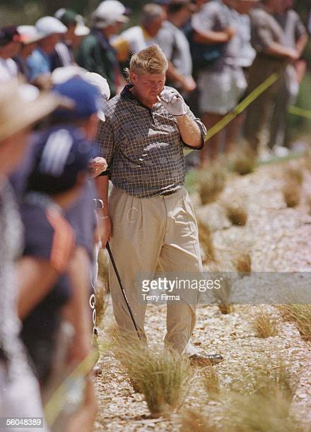 Big John Daly takes a puff on the obligatory fag as he waits on to hit out of the rough on day two of the World Cup Of Golf played at the Gulf...
