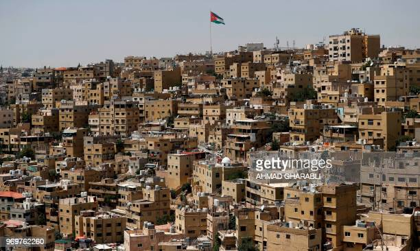 TOPSHOT A big Jordanian flag flutters in front of Amman's Jabal alQala district on June 8 2018 Jordan's authorities may have shelved a proposed...