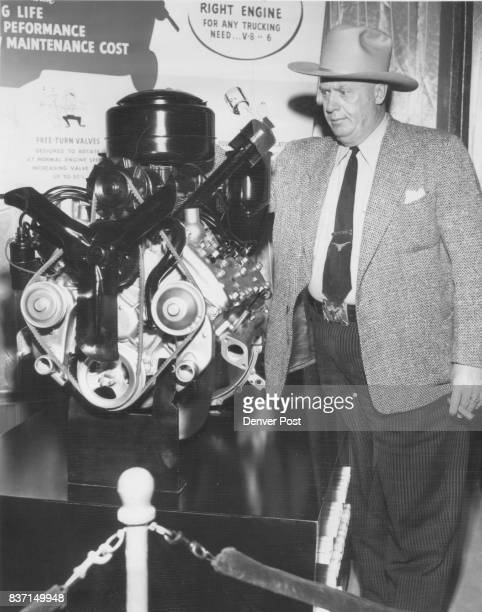 Big man and motor- Gilbert Carrel, chief of the Colorado highway patrol, inspects Ford V-8 engine during tour of show. Credit: Denver Post