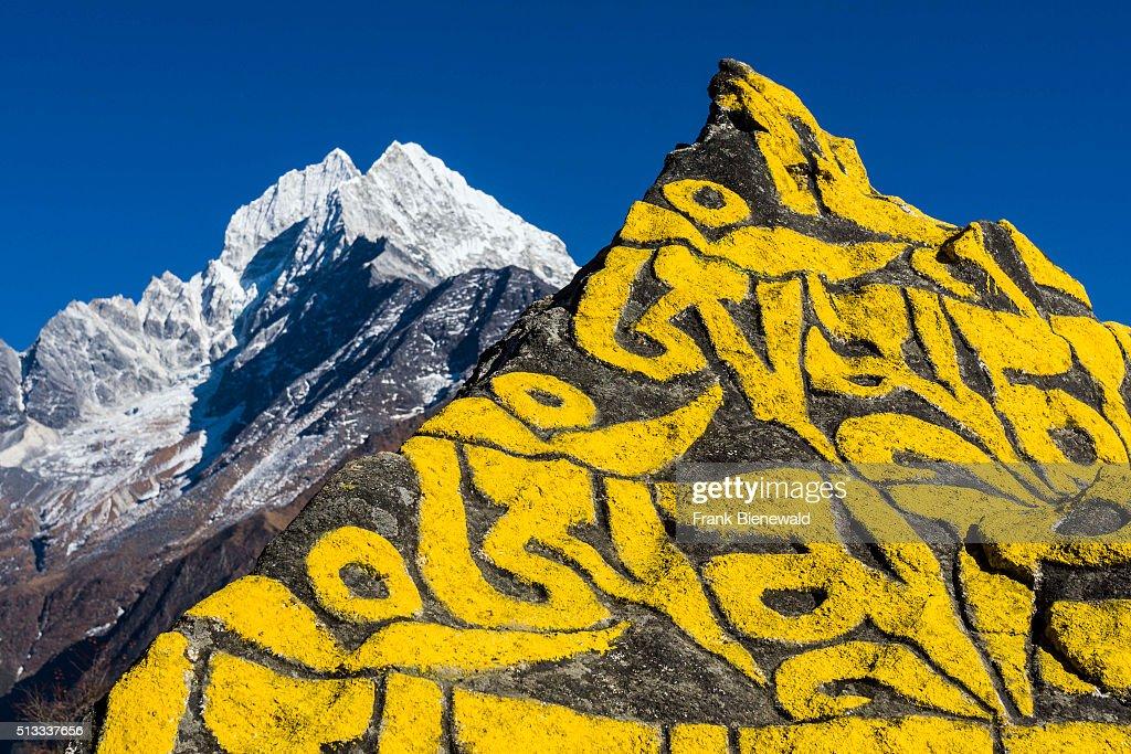 Big Mani stone with the tibetean mantra Om mani padme hum... : News Photo