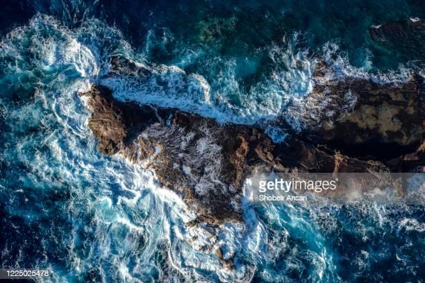 big ocean waves crashing into rocks in the ocean, maui, hawaii - fels stock-fotos und bilder
