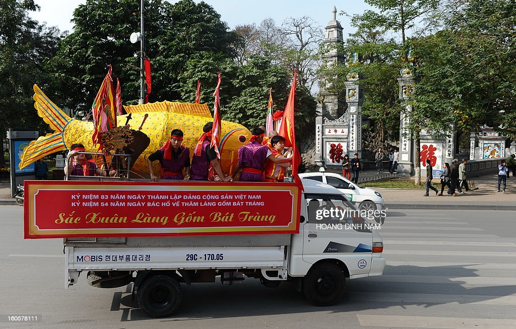 A big paper-made carp (in yellow) is transported on the back of a truck to a ceremony site to mark 'Kitchen God Day', part of the Lunar New Year or Tet celebrations by Vietnamese, in dowtown Hanoi on February 3, 2013. Vietnamese believe that Tet marks the time when the Kitchen God reports on their family to the Jade Emperor on the 23rd day of the 12th lunar month, meaning a week before Tet. On that day families usually burn gold leaf paper and offer live carp for him to ride. AFP PHOTO / HOANG DINH Nam