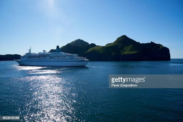 Big passenger ship sailing alongside Vestmannaeyjar (Western Islands) archipelago at sunset, Iceland