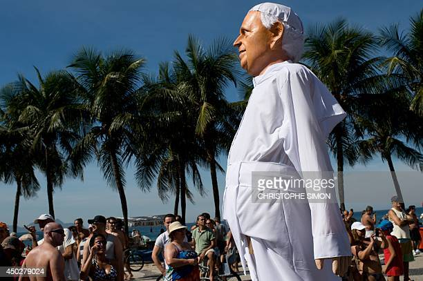A big puppet representing pope Francis is paraded along Copacabana Beach to welcome the World Cup in Rio de Janeiro Brazil on June 08 2014 AFP PHOTO...