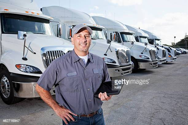 big rig trucks behind man holding tablet - trucking stock pictures, royalty-free photos & images