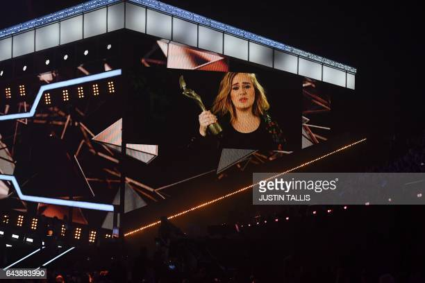 A big screen shows British singersongwriter Adele accepting the BRITs global success award during the BRIT Awards 2017 ceremony and live show in...